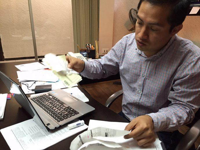Jorge Morales muestra los recibos de compra y pagos que ha hecho de su bolsa/Plumas Libres